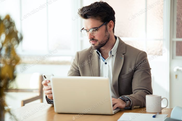 Handsome young business man using his smartphone while working with laptop in the office.