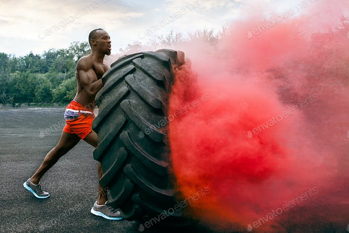 Handsome muscular man flipping big tire outdoor.