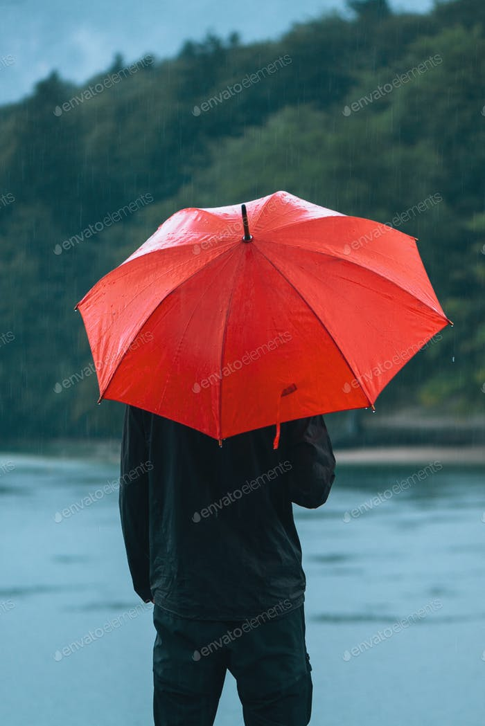 Man with red umbrella contemplates on rain