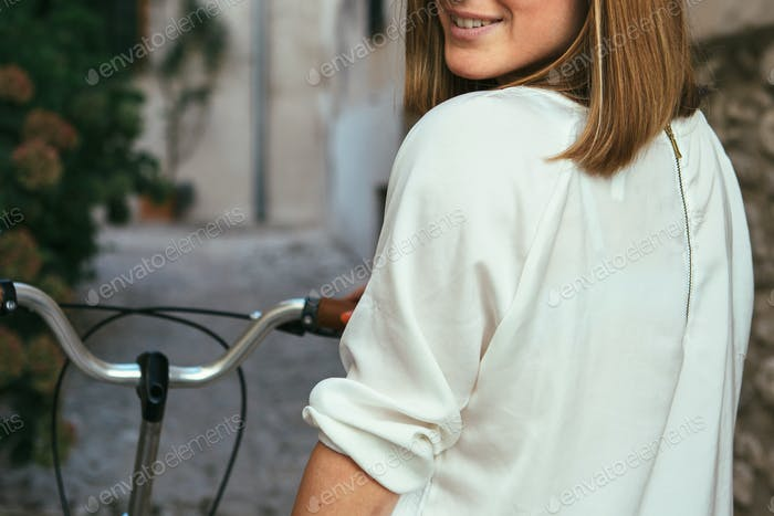 Crop female smiling on bike