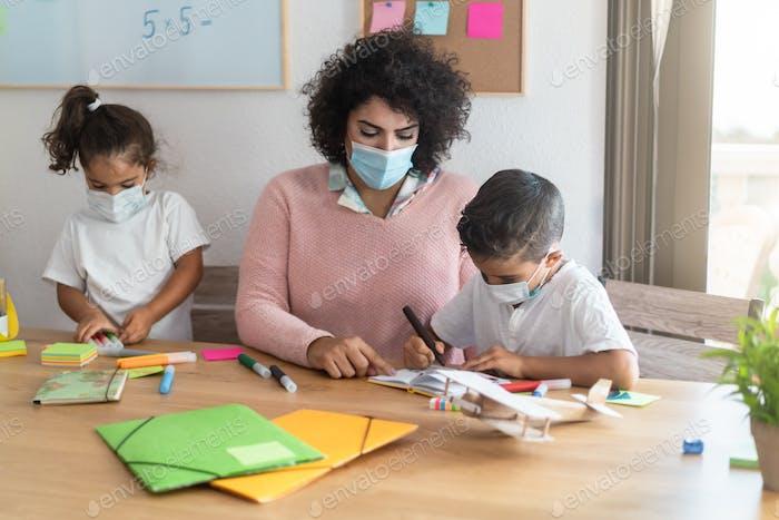 Teacher helping children inside preschool during coronavirus outbreak - Focus on boy face