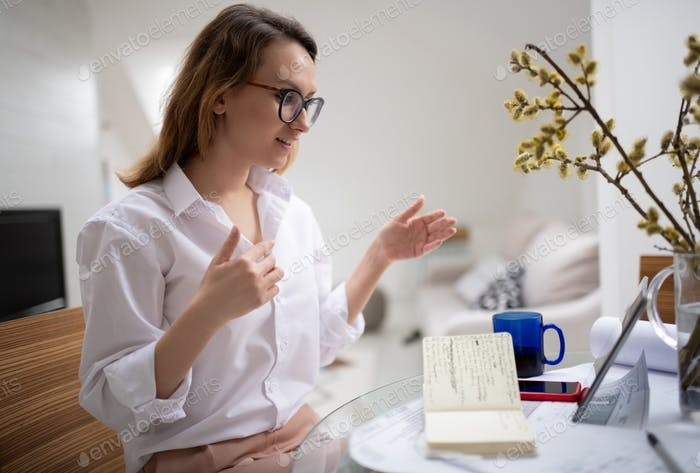 Positive businesswoman having online discussion with partner via tablet