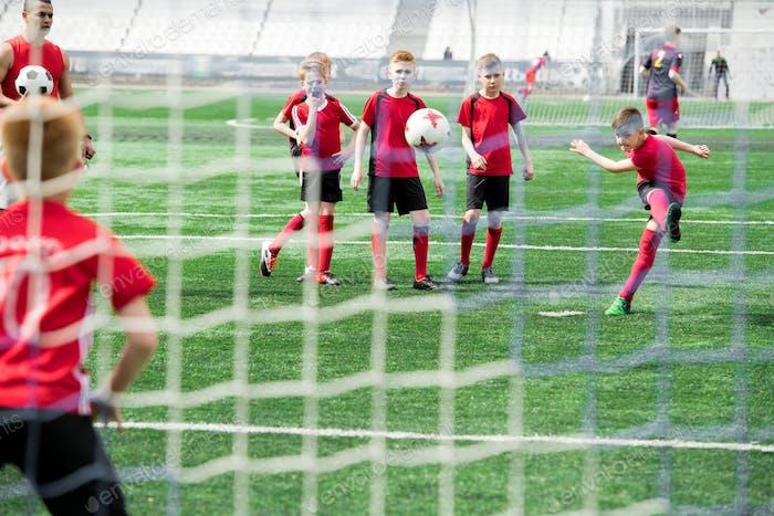 Boy Scoring Goal during Match