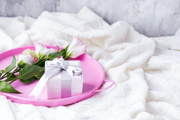 Geschenkbox und Pastellblüten Eustoma für Valentinstag oder Muttertag auf rosa Tablett auf dem Bett. Flache Lag