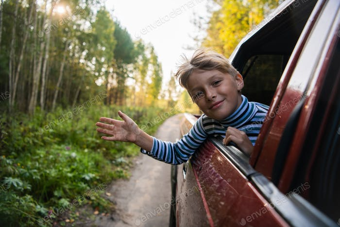 Cheerful child who is looking out of an open window of the car