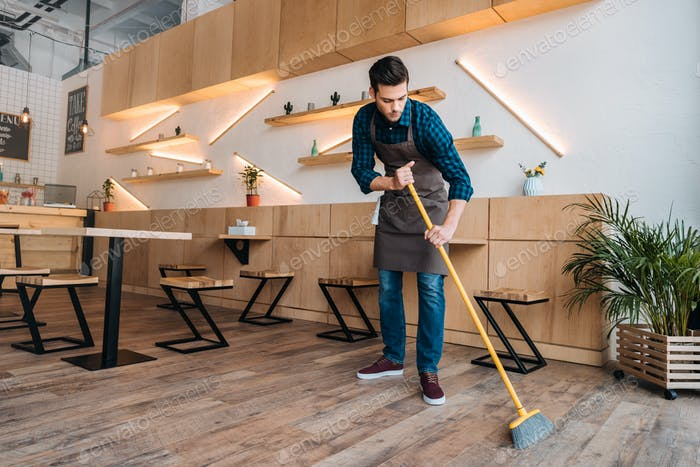 young worker in apron cleaning floor with sweep in restaurant