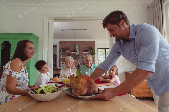 Front view of happy multi-generation Caucasian family having food on dining table at home