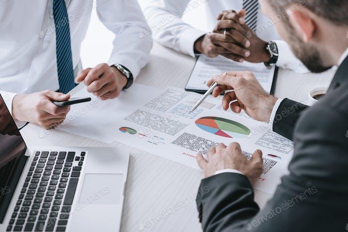 visión parcial de empresarios multiétnicos discutiendo un nuevo proyecto en el lugar de trabajo