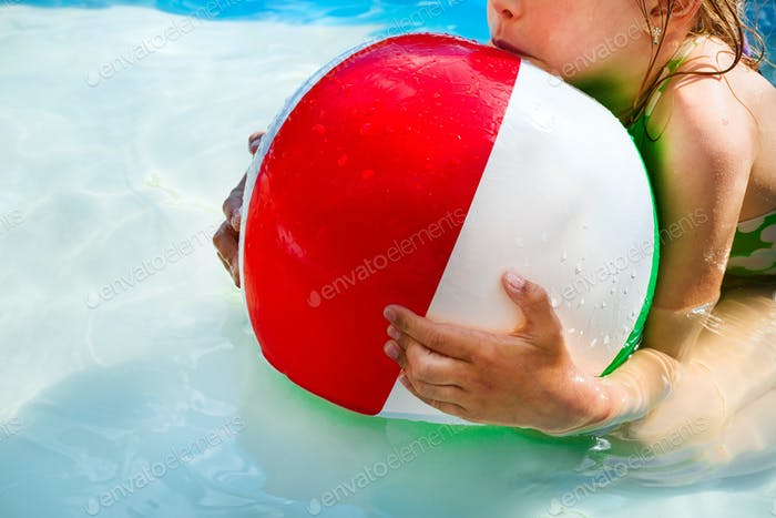 Little girl is playing with a ball in the pool into water on summer vacation in the courtyard