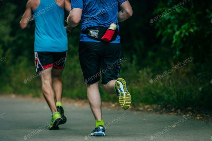zwei Athleten laufen durch den Park