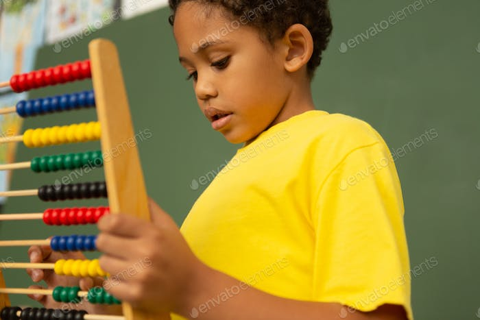 Schoolboy learning mathematics with abacus in a classroom at elementary school