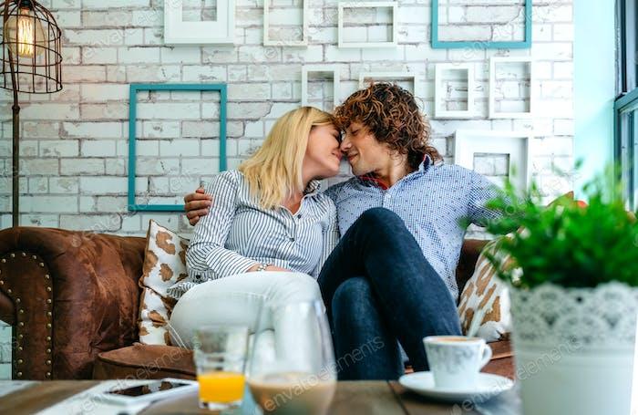 Pareja besándose en un sofá
