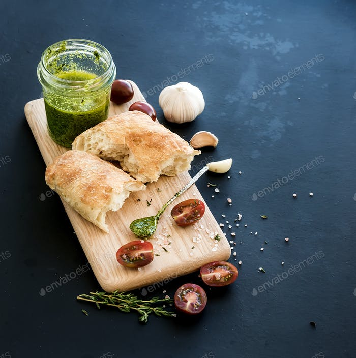 Pesto sauce in jar, ciabatta bread, cherry-tometoes, thyme and garlic on rustic wooden board