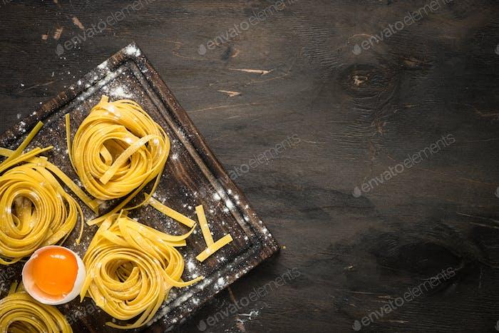 Prepartion homemade pasta tagliatelle at wooden table.