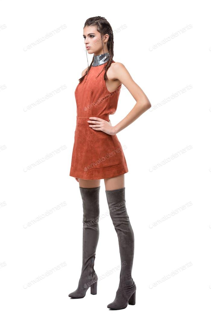 Junge Dame stehend und traumhaft beiseite in hellbraunem Kleid und kniehohen Stiefeln