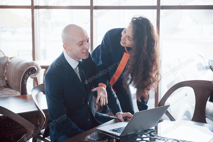 Junge schöne Frau, die mit Lächeln auf Laptop zeigt und etwas mit ihrem Kollegen besprechen