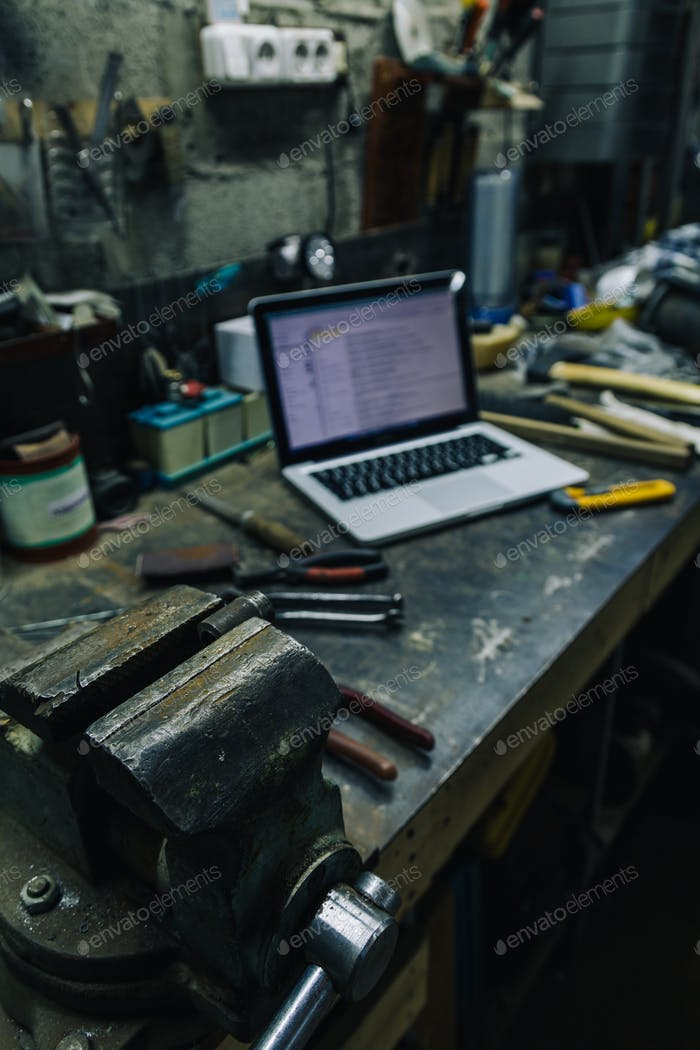 View of old tools,laptop and phone on table