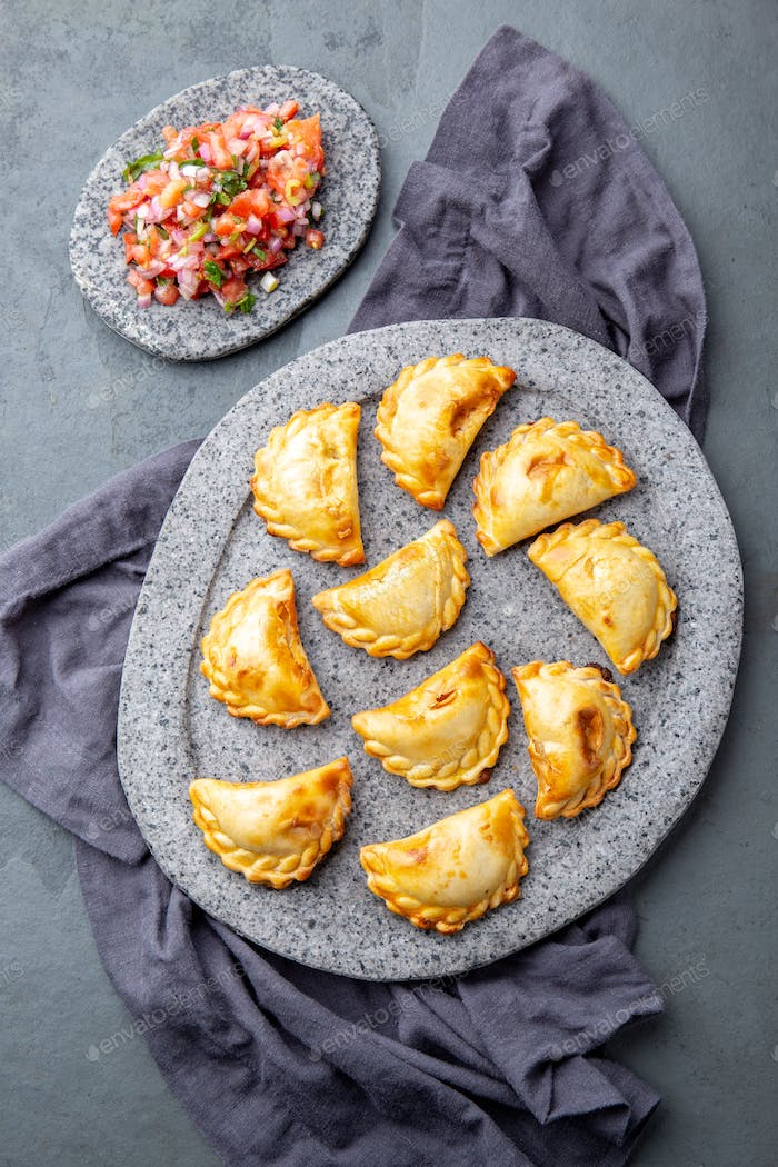 empanadas with ground meat on gray plate