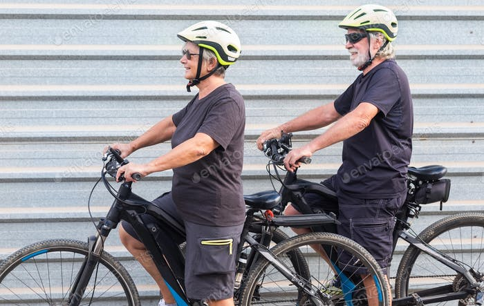Happy senior couple doing together outdoor activity with electric bicycle. Healthy lifestyle.