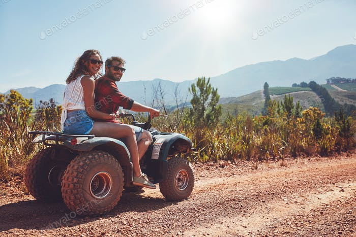 Couple enjoying a quad bike ride in countryside