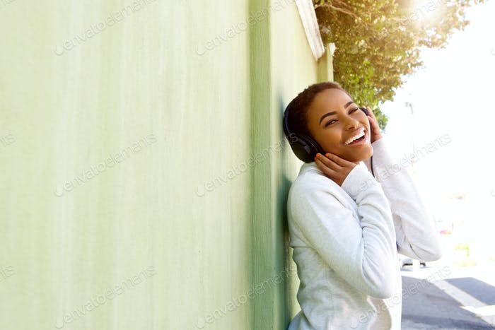 Young black woman enjoying listening to music with headphones