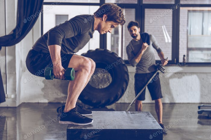 Muscular young men in sportswear exercising at gym workout