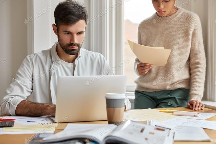 Indoor shot of serious man wants to deposite money in bank, reads job description on laptop computer