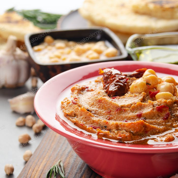 Hummus in clay dish topped with olive oil, chickpeas, spices and sun dried tomatoes on stone table