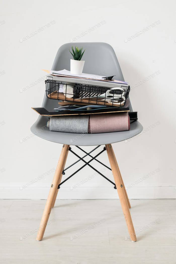 Grey chair with stack of office supplies or stuff of designer of interior