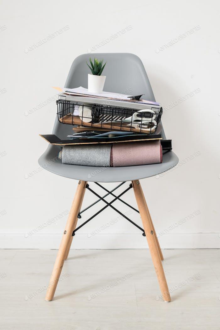 Grau Stuhl mit Stapel von Bürobedarf oder Sachen Designer von Interieur