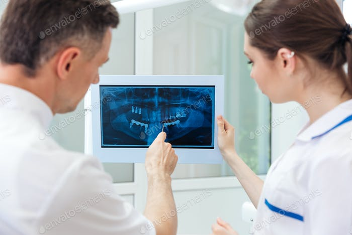 Male dentist showing something on the computer monitor