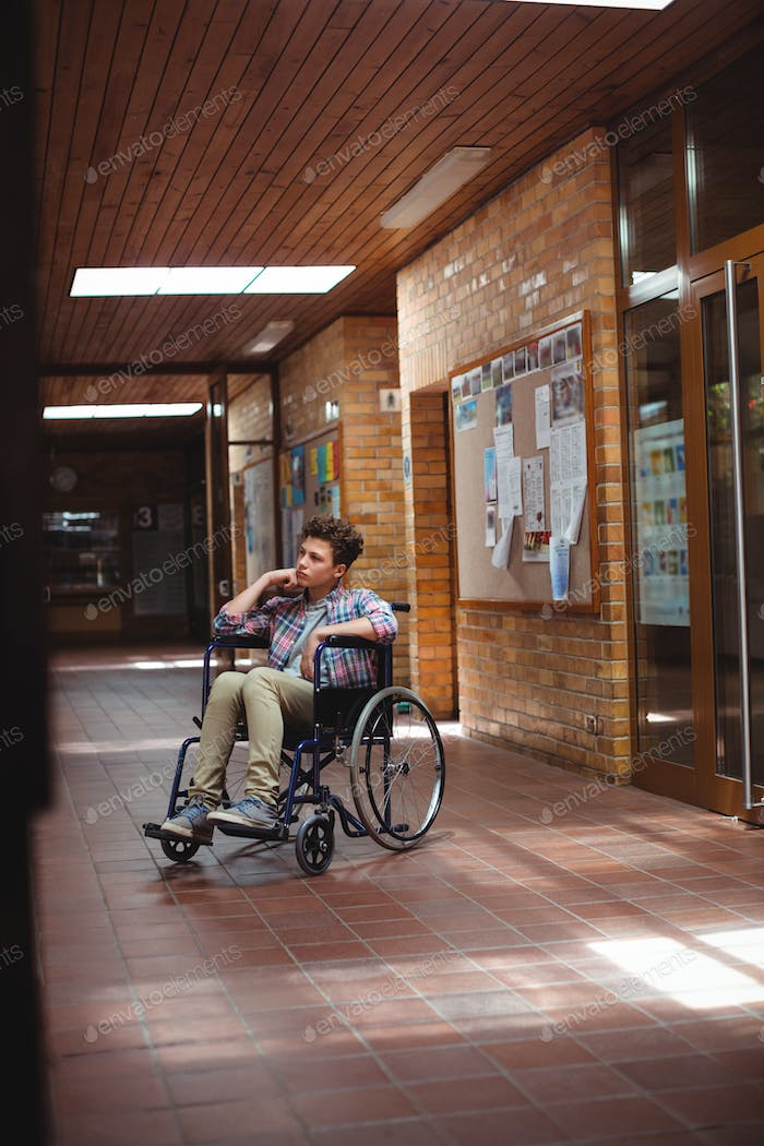 Disabled schoolboy on wheelchair in corridor at school