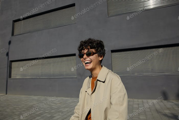Outdoor shot of pretty happy curly brunette woman in vintage sunglasses and beige trench coat