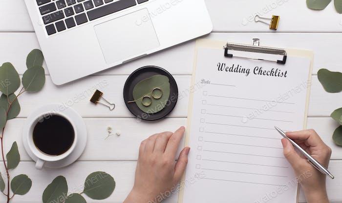 Woman worker writing wedding checklist for bride
