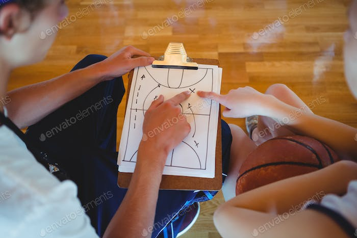 Coach explaining diagram to female basketball player