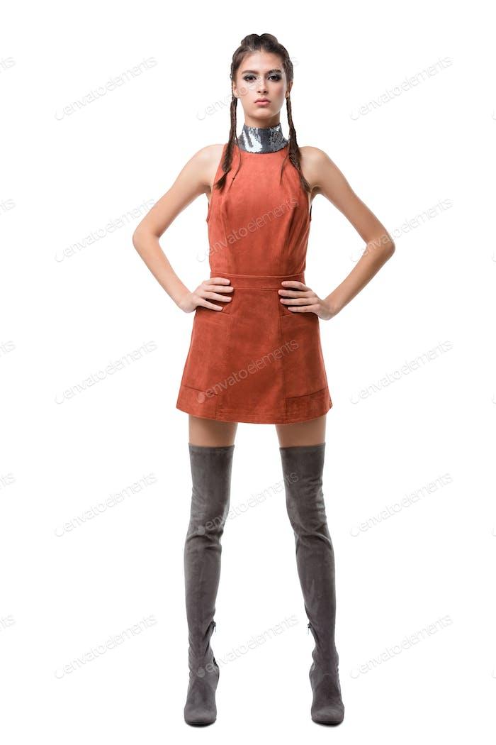 Junge hübsche Dame stehend in hellbraunem Kleid und kniehohe Stiefel auf weißem Hintergrund