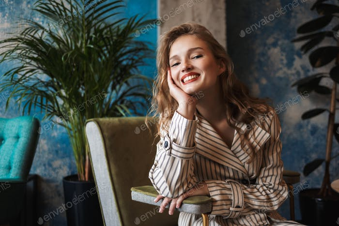 Young cheerful woman with wavy hair in striped trench coat leani