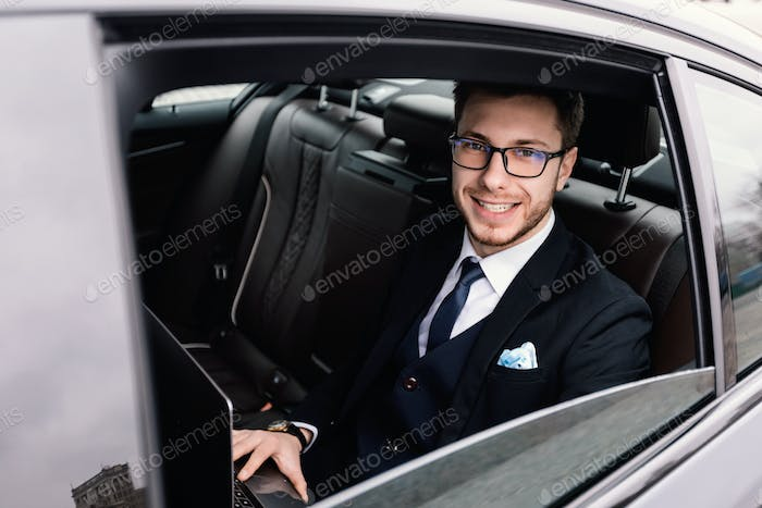 Businessman sitting in car with pc looking out of window