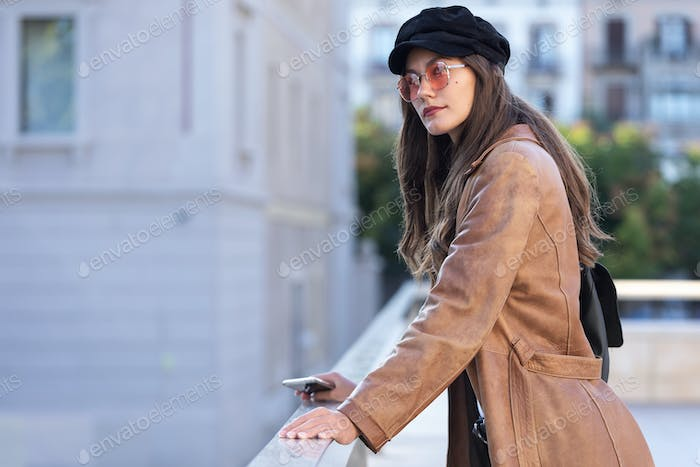 Pretty young woman looking to sideways while leaning on a railing in the street.