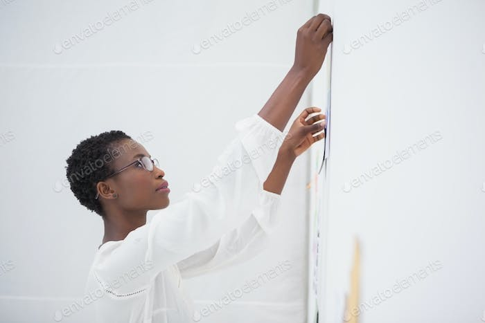 Businesswoman with glasses pinning paper up in the office