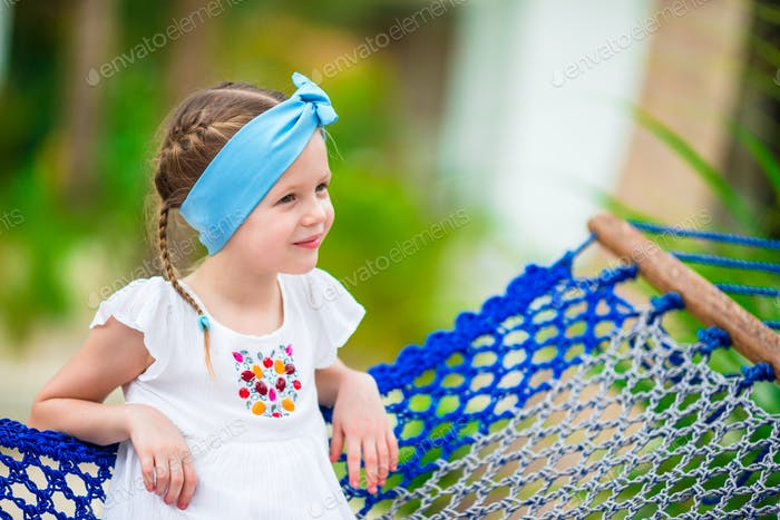 Adorable little girl in hammock outdoor at the beach
