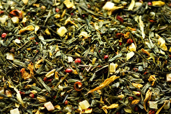 Texture of green tea with dried petals yellow flowers and red pepper. Food background. Organic
