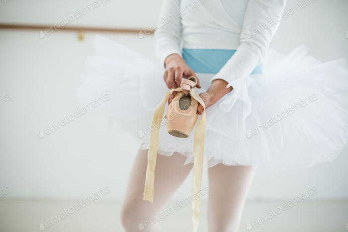 Mid section of ballerina holding ballet shoes