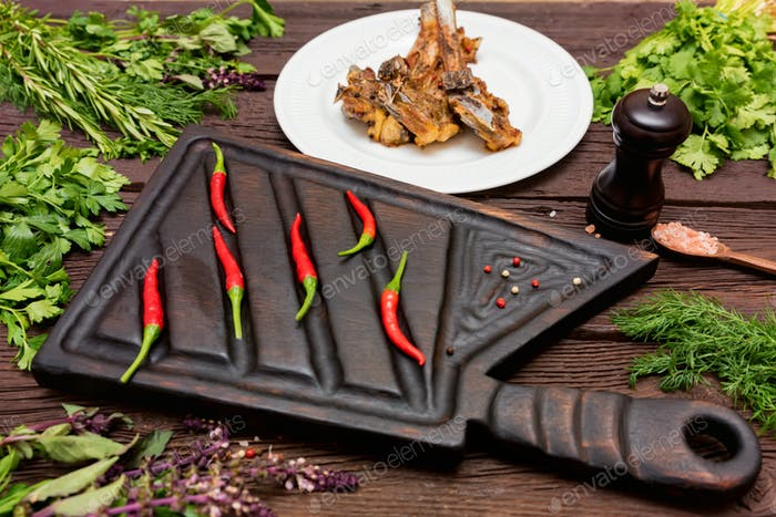 Roasted lamb ribs served on plate and cutting board with chili pepper