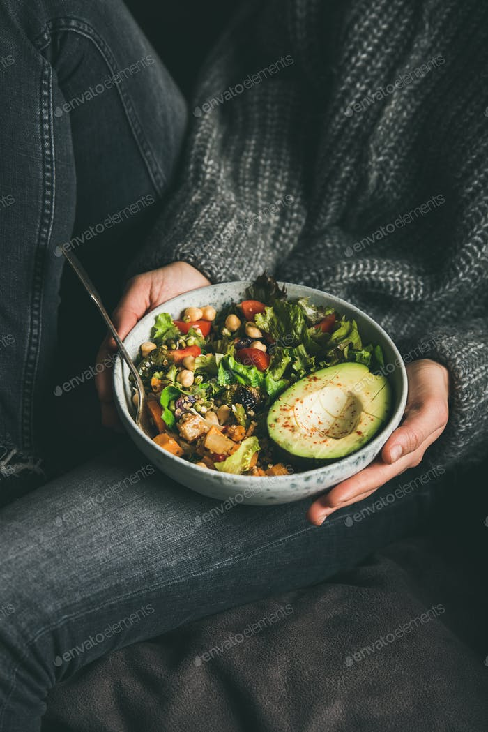 Woman holding bowl with fresh salad, avocado, beans and vegetables