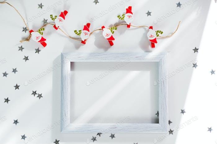 Fröhliche Weihnachten und Neujahr Rahmen-Mockup. Weihnachtsmann, silberner Stern und weißer Bilderrahmen auf