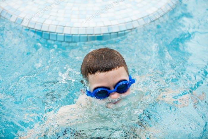 Kind in einem Schwimmbad Auftauchen aus Wasser