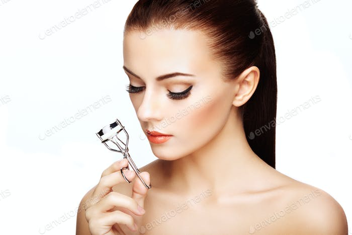 Portrait of beautiful woman making curl eyelashes. Beautiful wom
