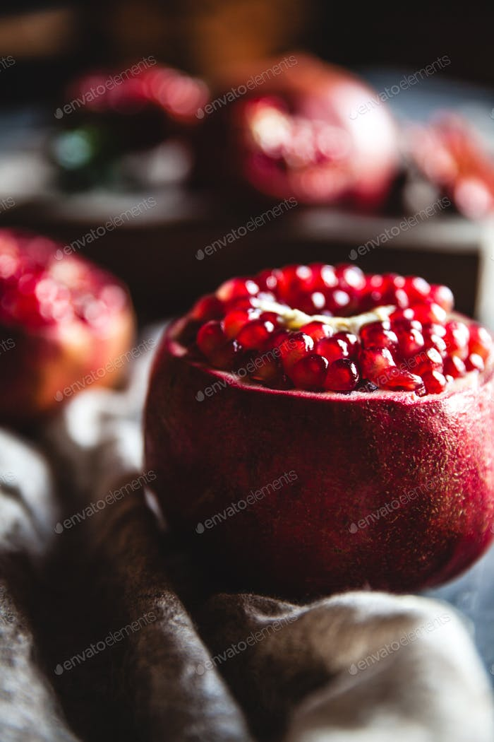 Fresh pomegranate in a wooden box. On a gray background. Top view. Copy space