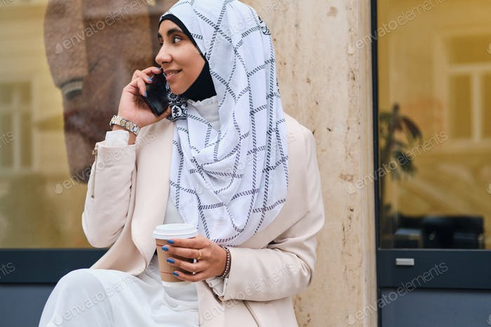 Side view of pretty Arabic woman in hijab with coffee to go talking on smartphone on city street